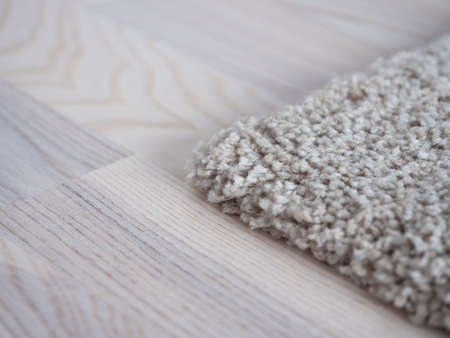 Image of white carpet on the light wooden parquet floor