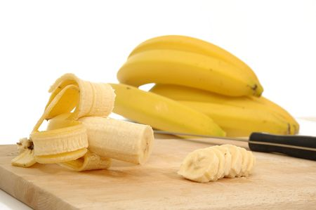 bananas on carving board on white background photo
