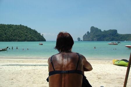 Woman sitting on a beach in Thailand enjoying the view photo