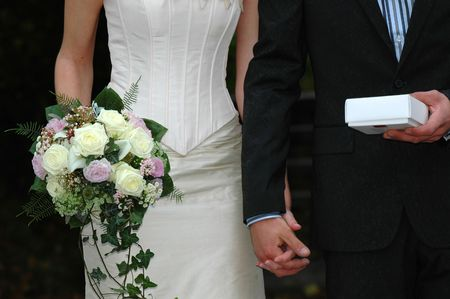 Wedding couple are holding a bouquet and a gift. photo