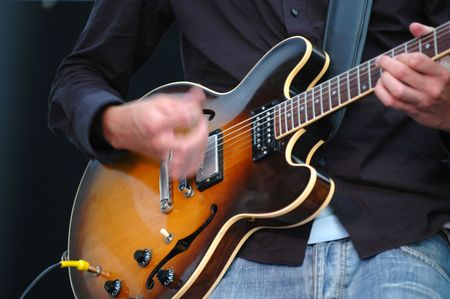 Man playing his guitar. Note his hand is in motion. Stock Photo - 710342