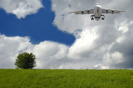 Plane is flying over a very beautiful hill with a green tree. The main focus is on the plane. photo