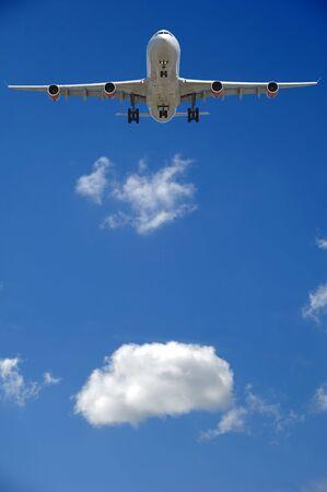 Avión se va a la tierra. Una nube blanca se encuentra en el fondo. Foto de archivo