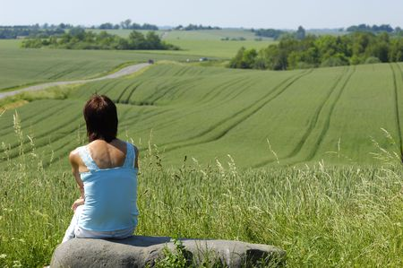 living idyll: Woman is sitting on a stone looking a the view
