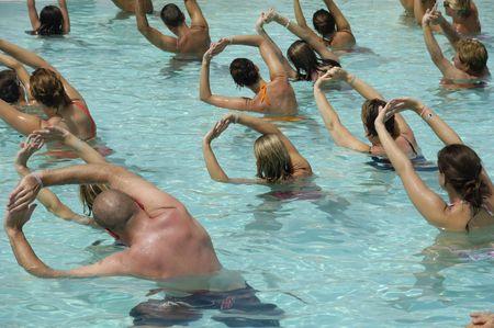 mucha gente: Muchas personas que hacen deporte en una piscina