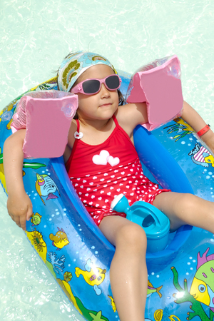 Young child is relaxing in gummiboat in swimming pool. photo