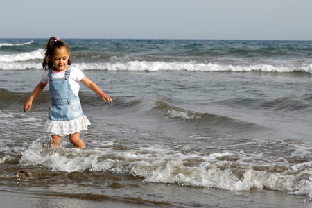 Child is standing in the big ocean alone. photo