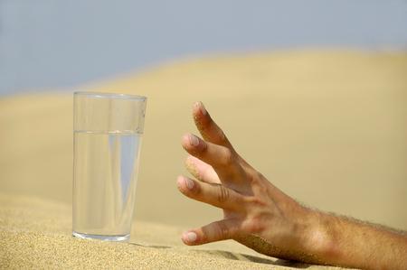 sediento: Está llegando a las manos de un fresco vaso de agua fría en el desierto.  Foto de archivo