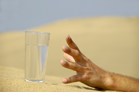 the dying: Hand is reaching for a fresh glass of cold water in desert.