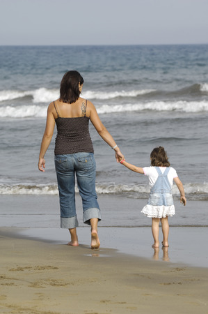 Mother and her child is walking at the beach. photo