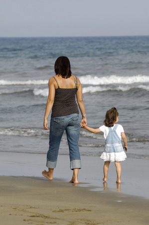 Mother and daughter together at the beach.  photo