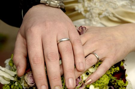 Two wedding hands with rings and flowers. photo