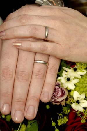 Wedding hands with rings and flowers photo