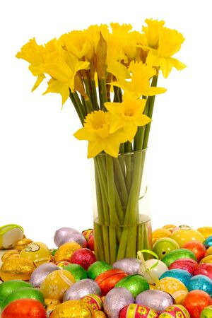 Daffodils in vase with many easter eggs taken on a clean white background. photo