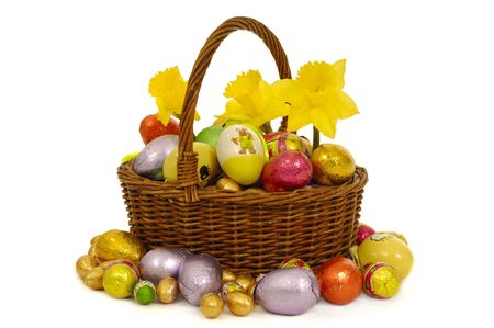 Easter basket with eggs and flowers. Taken on a  white background. photo