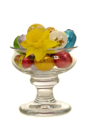 Easter eggs and flower in a big glass. photo