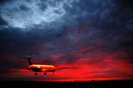 Plane is flying while the sun is setting Stock Photo - 2920780