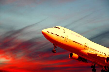 Plane is flying while the sun is setting Stock Photo