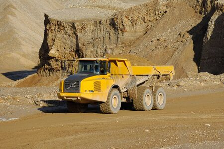 A yellow dump truck is driving in a mine photo