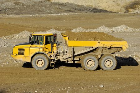 A yellow dump truck is driving in mine photo