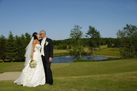A wedding couple is kissing  photo