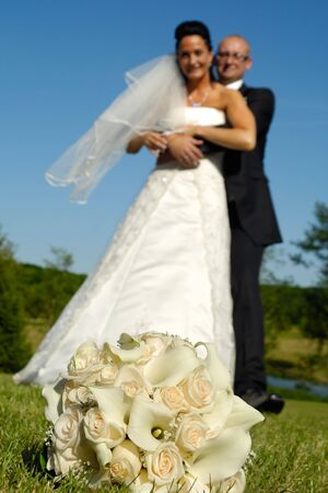 Wedding bouquet in focus and couple in blur photo