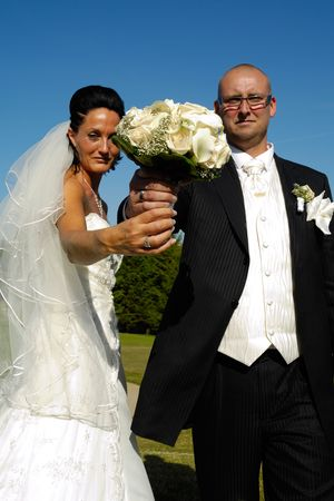 Bride and groom is holding the wedding bouquet together. Focus on the bouquet. Stock Photo - 3216458