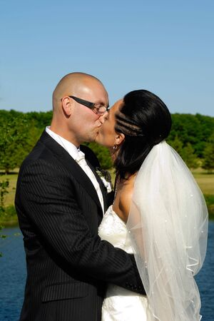 Bride and groom is kissing by the lake. photo