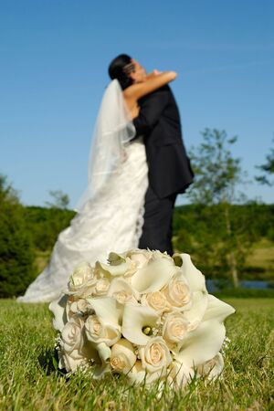 Wedding bouquet in focus and couple in the background holding each other. photo