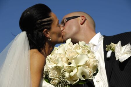 Bride and groom is kissing while showing the bouquet. The focus is on the flowers the couple are in blur photo