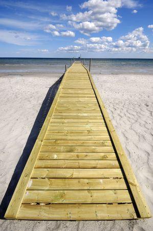 blu sky: Long bridge on beach. The sky is blu with clouds.