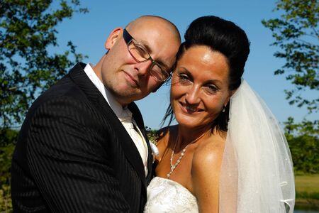 A very happy wedding couple standing close together. photo