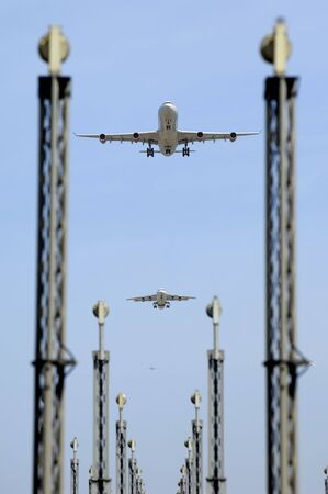 Planes are flying over landing lights in an airport Stock Photo - 3385652