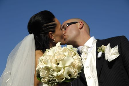 Bride and groom is kissing while showing their bouquet. Please note that the focus is on the flowers. photo