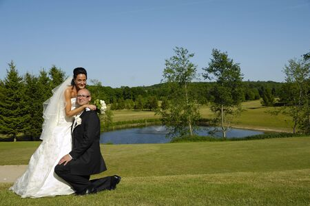 Groom is on his knee of his bride photo