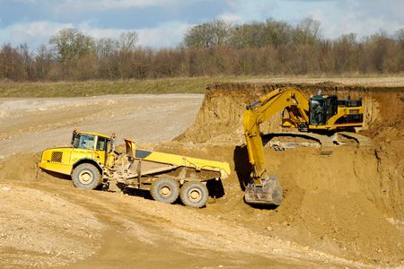 Yelloow truck and digger are working in mine photo