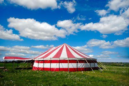 Una carpa de circo con rayas rojas y blancas en la naturaleza verde. El cielo es azul con nubes cúmulus blanco