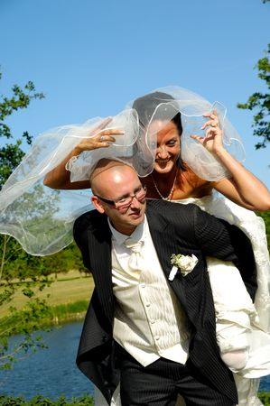Groom is lifting his bride up in a park. photo