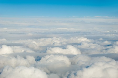 White clouds taken form above while flying in a plane. photo
