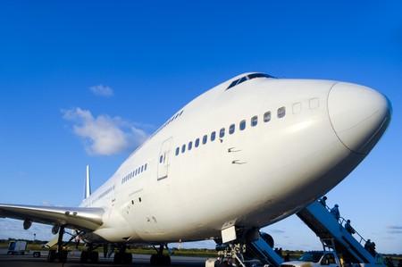 Viajes en avión - un avión aparcada está cargando frente a los pasajeros en un aeropuerto  Foto de archivo