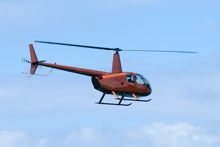 Orange helicopter is flying in blue sky photo
