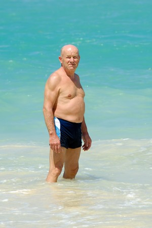 Un hombre senior está de pie en el agua va a nadar. Playa en Punta Cana, República Dominicana.