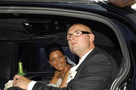 Happy wedding couple sitting in fine car. photo