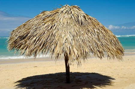 Parasol made out of palm leafs on beach. Stock Photo - 7637187