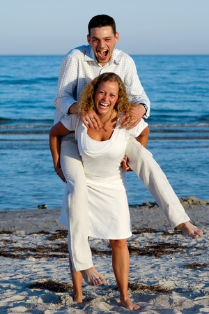 A happy woman and man having fun on beach.  photo