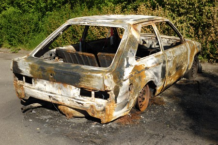 abandoned car: A car wreck which have been burnt out.