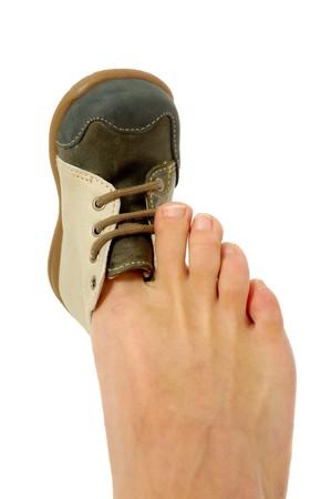 Un adolt es tratar de ajustar un zapato de bebé.  Foto de archivo