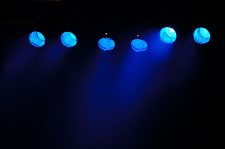 performace: Lights and smoke. Row of blue lights from a stage.