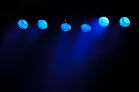 fari da palco: Luci e fumo. Riga di luci blu da un palcoscenico.  Archivio Fotografico