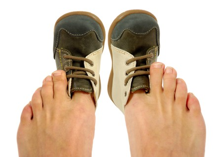 An adolt is trying to fit a baby shoe.